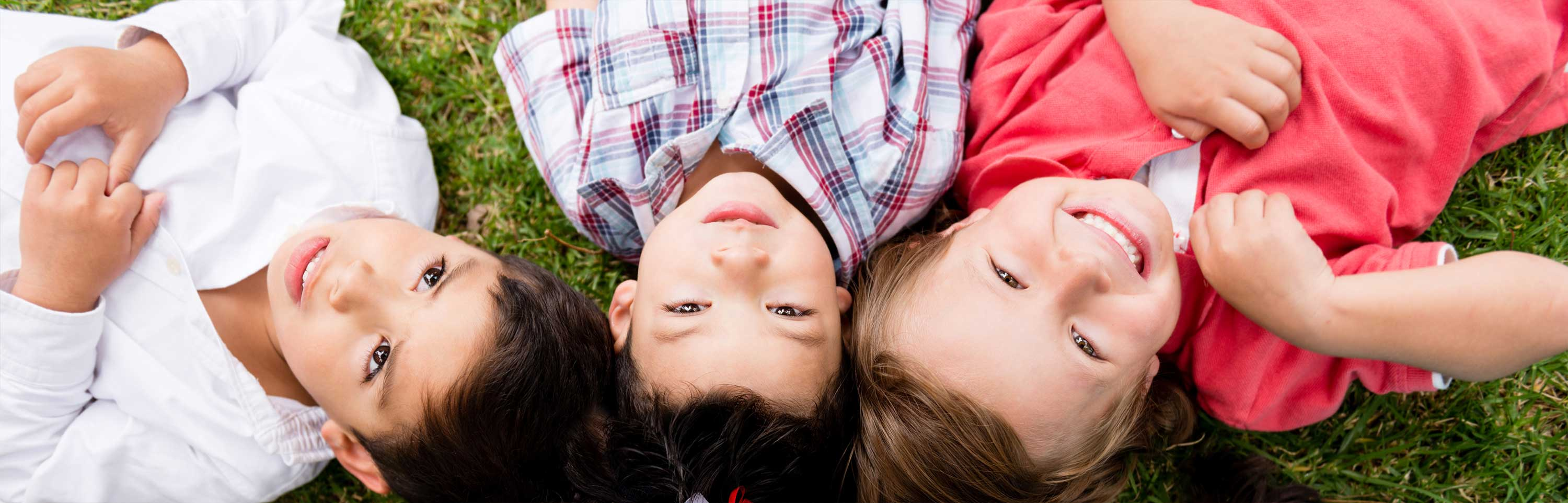 Children lay on the grass at the park