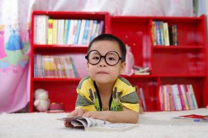 Little boy in glasses reading a book