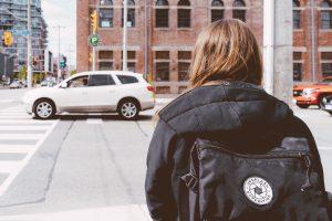 A girl looks across a busy street