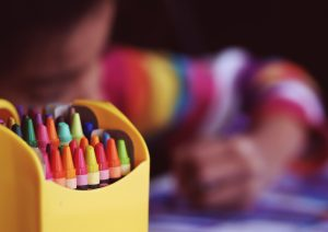 A box of crayons in front of children drawing